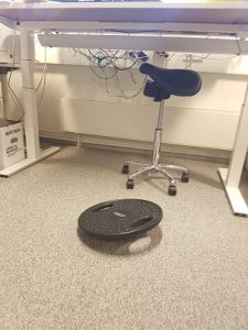 Tasapainolauta, jonka päällä voi harjoitella kehon hallintaa samalla kun tekee töitä näyttöpäätteellä. Satulatuoli on piilossa työpöydän alla satunnaista istumista varten.